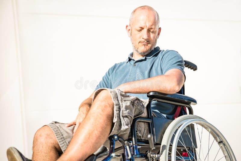 有障碍的残疾人在消沉片刻的轮椅 库存照片