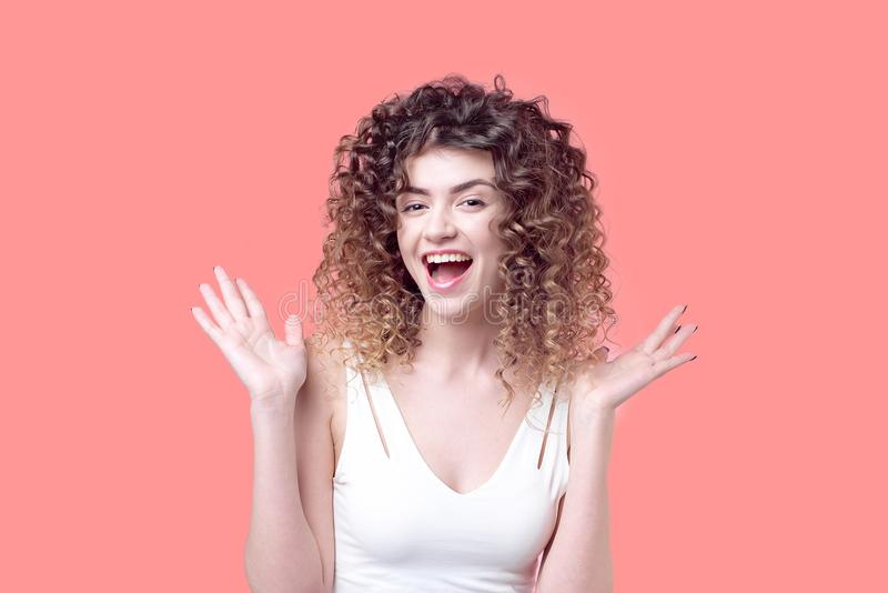 有难以置信的卷毛微笑的美丽的女孩惊奇 免版税图库摄影