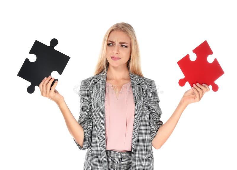 有难题片断的混乱的年轻女实业家在白色背景的 免版税库存照片