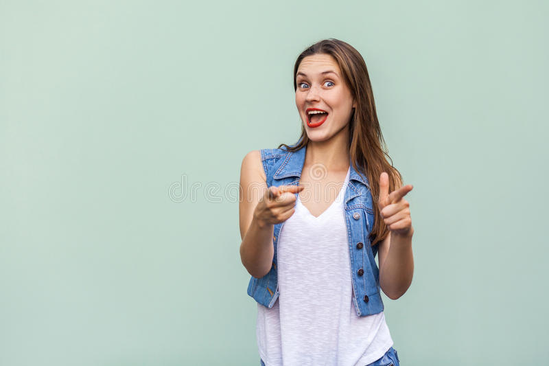 有雀斑、便装样式白色T恤杉和看照相机的牛仔裤夹克的愉快的快乐的十几岁的女孩 库存图片