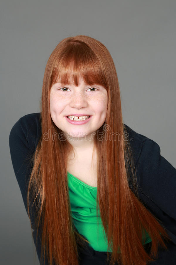 有雀斑和笑涡的青春期前的红头发人女孩 免版税图库摄影