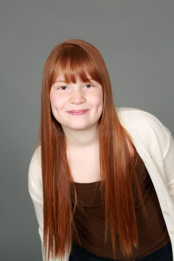 有雀斑和笑涡的青春期前的红头发人女孩 免版税库存照片