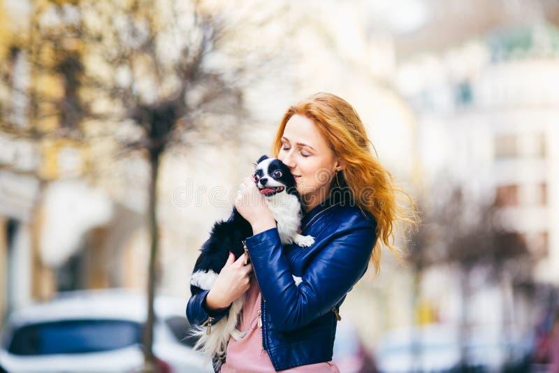 有雀斑的一名年轻红发白种人妇女举行和亲吻,拥抱奇瓦瓦狗品种黑白卷毛狗  女孩博士 免版税库存图片