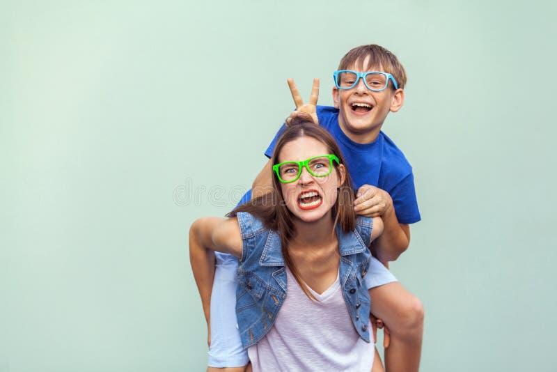 有雀斑的兄弟爬上了在一个更老的逗人喜爱的姐妹背面 做滑稽的疯狂的面孔和看照相机 图库摄影