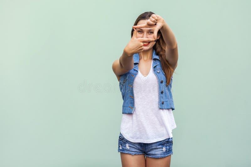 有雀斑的创造性的年轻妇女,做与她的手指的一个框架姿态,她通过看得形象化项目 库存图片