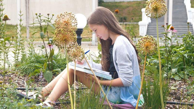 有雀斑的小女孩在公园画坐在灌木 库存图片