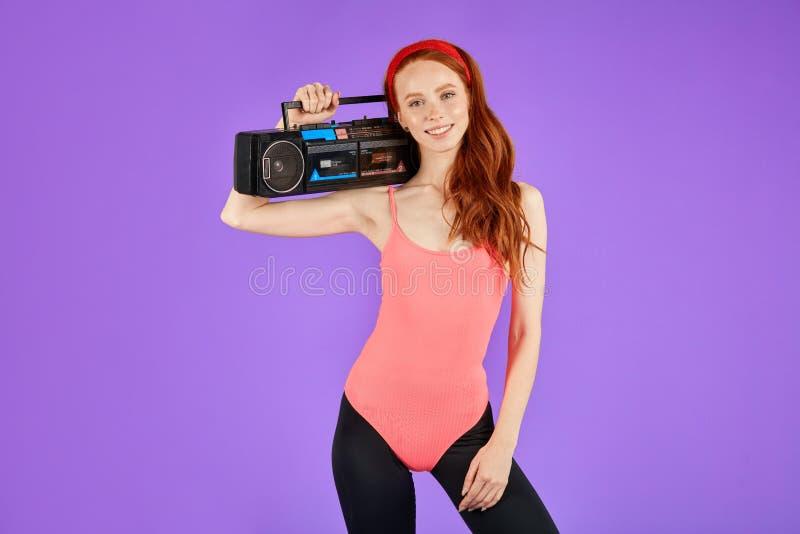 有雀斑的年轻女人在与快乐的微笑的照相机看,拿着卡式磁带播放机 免版税库存图片