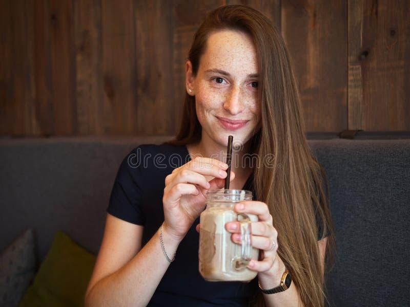 有雀斑的画象年轻愉快的美丽的红头发人妇女喝在咖啡馆的咖啡在咖啡休息 图库摄影