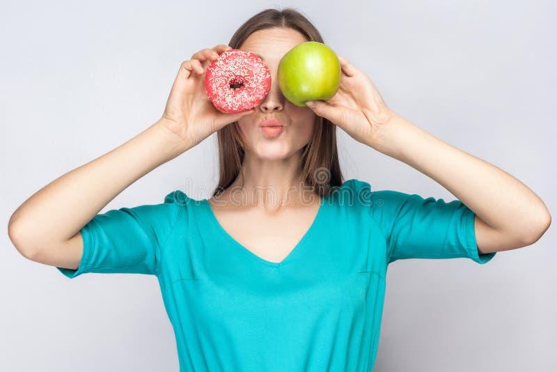 有雀斑的美丽的少妇在绿色礼服,举行在她眼睛绿色苹果前和桃红色多福饼和亲吻 库存照片