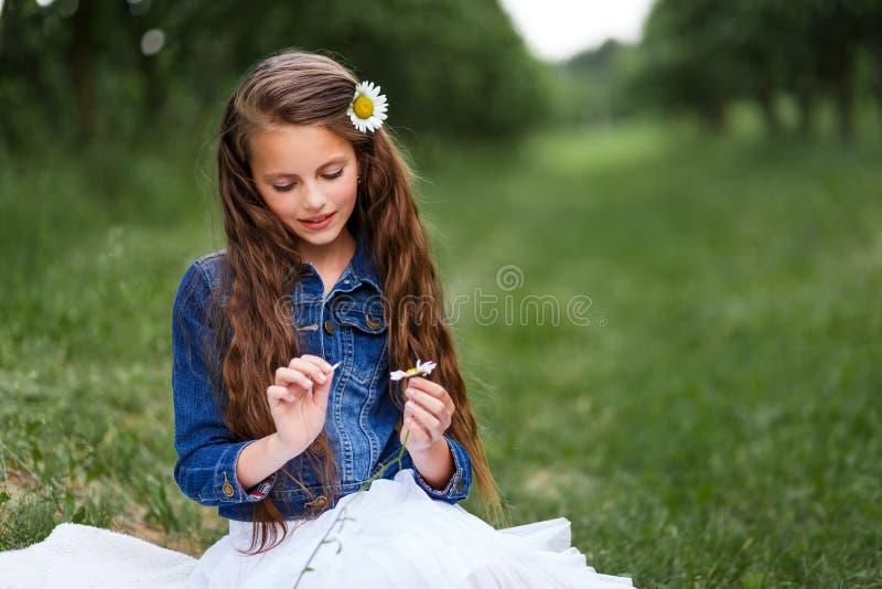 有雏菊和一朵花花束的逗人喜爱的微笑的女孩在头发 有一束的女孩春黄菊 免版税图库摄影