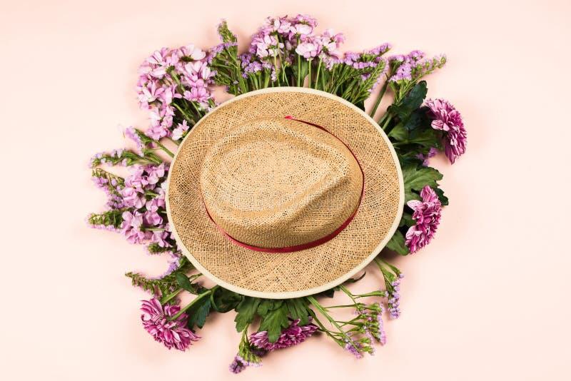 有雏菊和菊花美丽的花花束的草帽  免版税库存照片