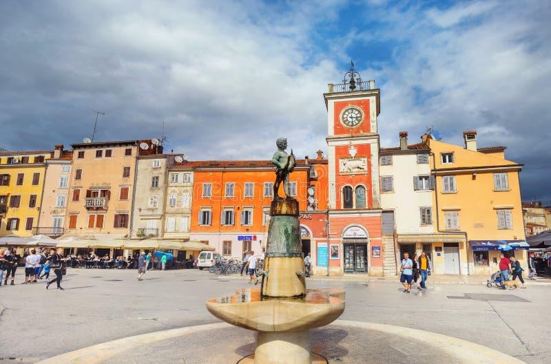 有雕塑的喷泉和在罗维尼镇大广场的钟楼  Istria,克罗地亚 免版税库存照片