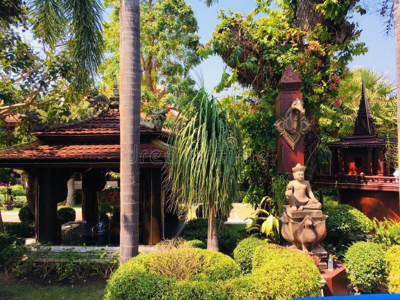 有雕象和热带树的庭院 免版税图库摄影