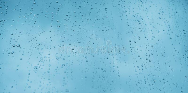 有雨珠背景纹理水平的顶视图被隔绝的蓝色玻璃,在窗口背景的雨,浅兰的天空,清楚的wate 免版税库存图片