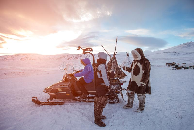 有雪上电车的人们在冻结的北部沙漠在日落的 免版税库存图片