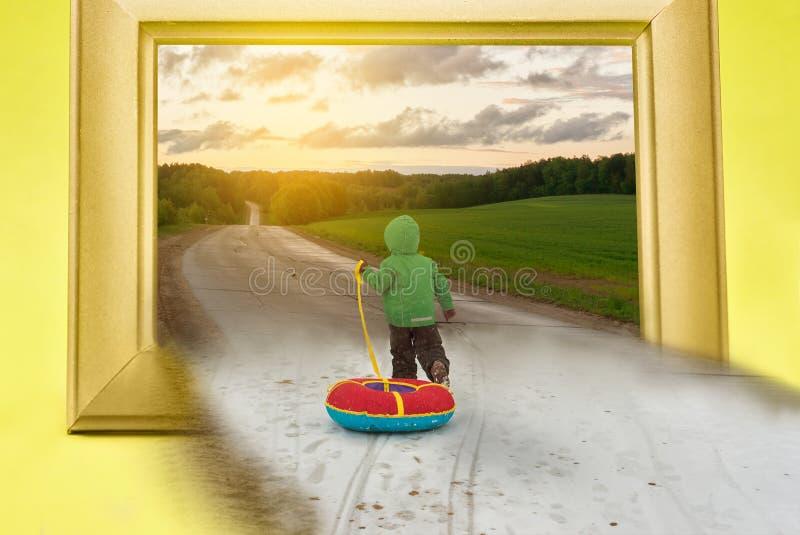 有雪撬奔跑的小男孩在往春天的冬天 温暖等待的概念 图库摄影