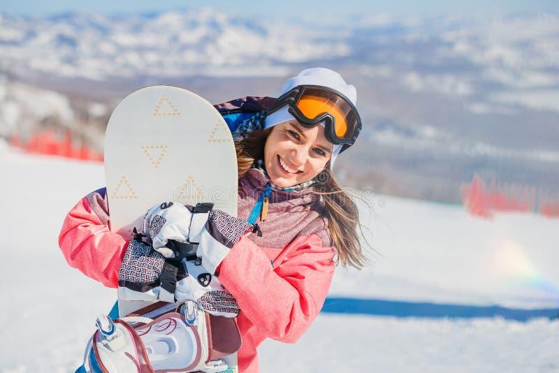 有雪板运动的微笑的少妇在山在冬天 库存照片