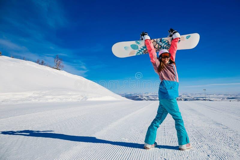 有雪板运动的快乐的妇女在山在冬天 免版税库存图片