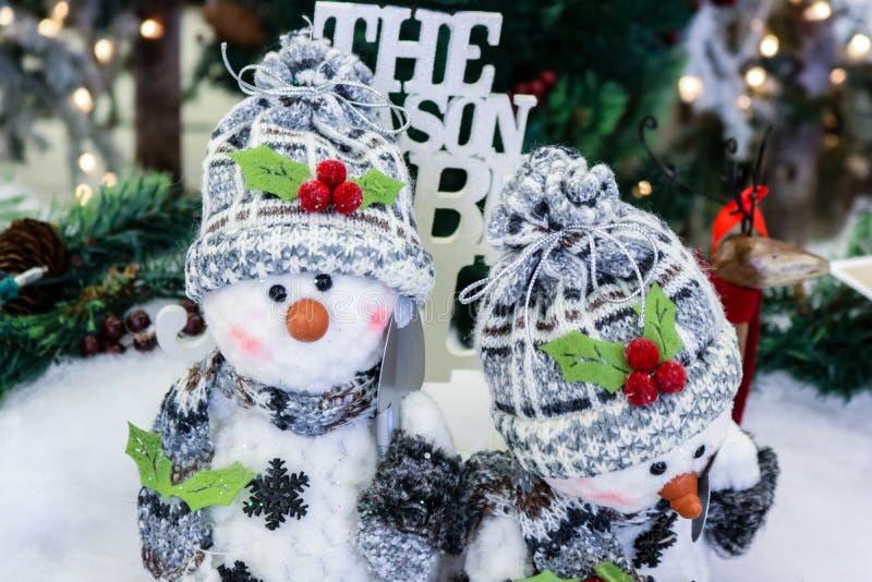 有雪的两个可爱的装饰雪人铲起盖帽和围巾在被弄脏的圣诞节背景前面 免版税库存图片