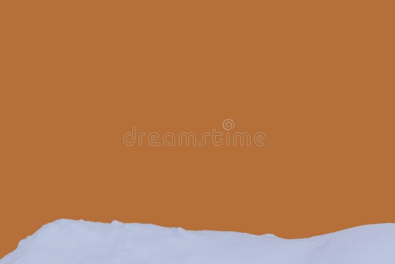 有雪的橙色墙壁在前景 免版税库存照片