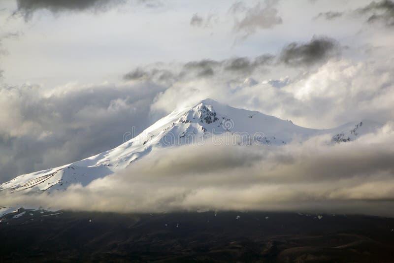 有雪的瑙鲁霍伊火山在顶面和剧烈的风雨如磐的云彩 免版税库存照片