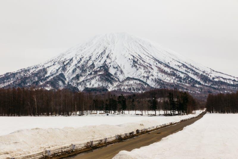 有雪的登上Yotei和积雪在与道路方式的地面上导致山在冬天在北海道,日本 图库摄影