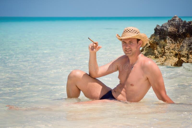 有雪茄的愉快的成功的英俊的人在海滩,大西洋,古巴,毛发的Playa, Cayo吉列尔莫 库存图片