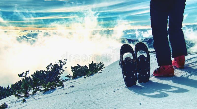 有雪靴的人腿在冬天山的雪走 免版税库存照片