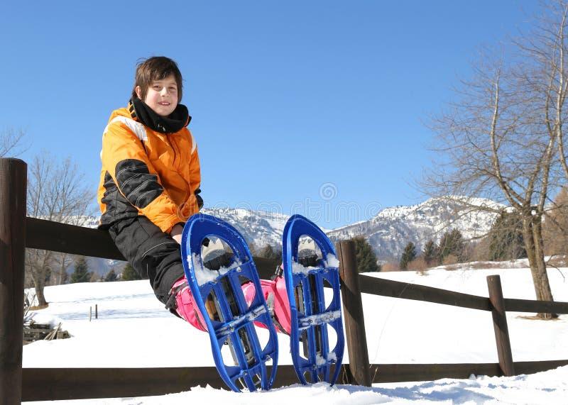 有雪靴的孩子在山 免版税库存图片