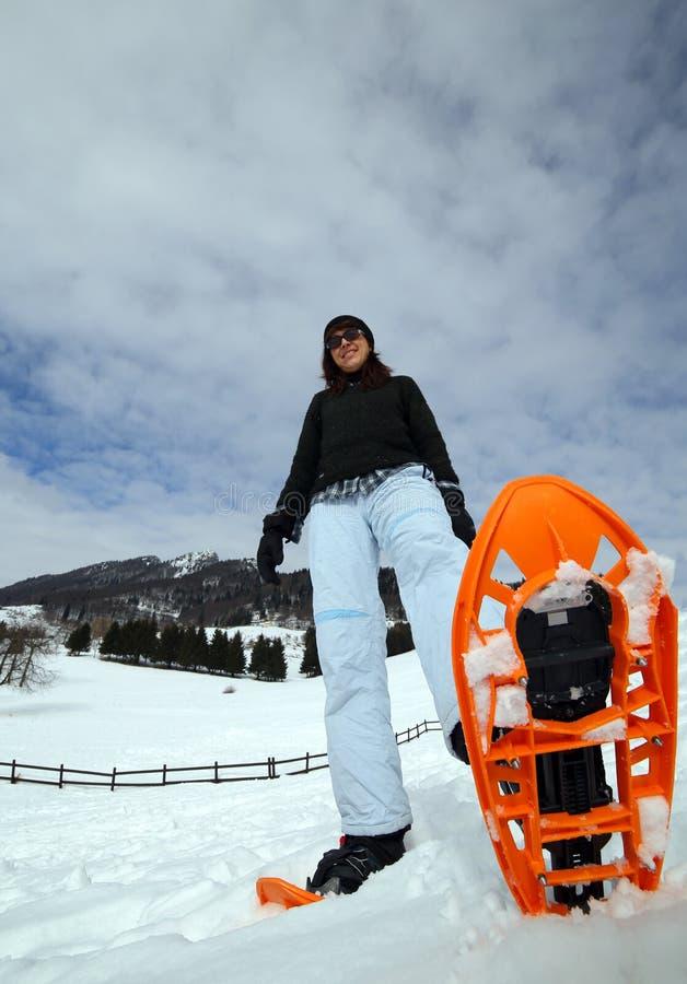 有雪靴的美丽的妇女在雪 免版税图库摄影