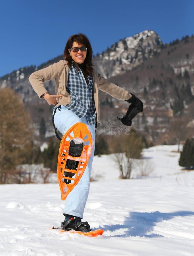 有雪靴的美丽的微笑的妇女在冬天 免版税库存图片