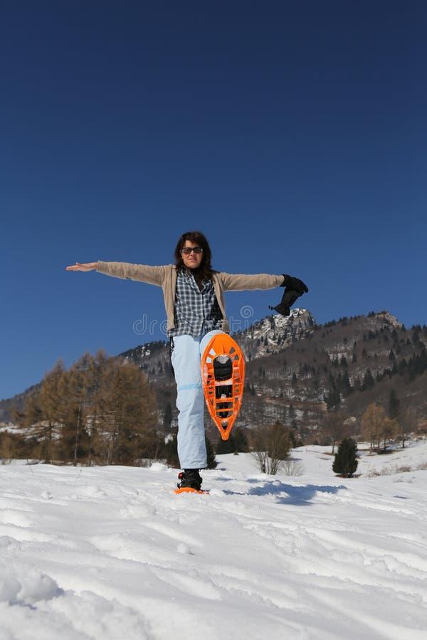 有雪靴的美丽的微笑的妇女在冬天 库存图片