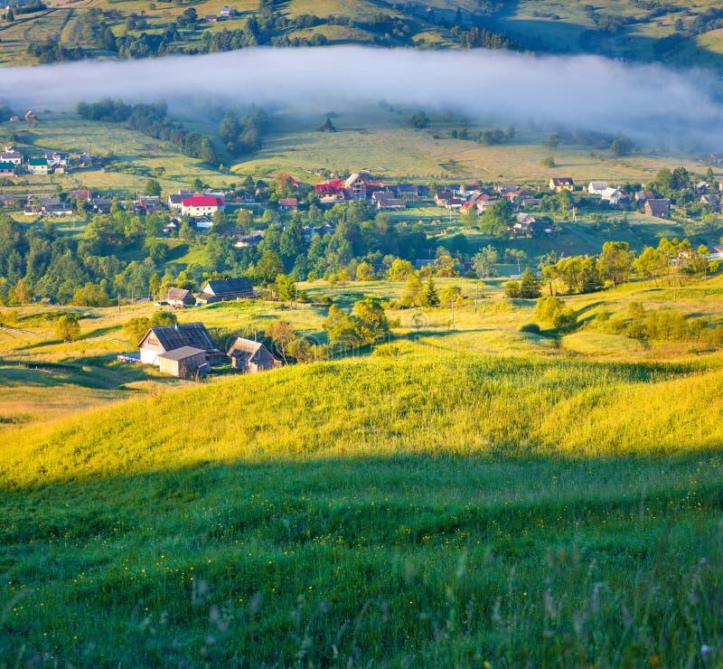 有雾的夏天早晨在山村 库存照片