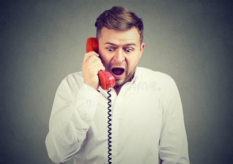有震惊的人在电话的新闻 免版税库存照片