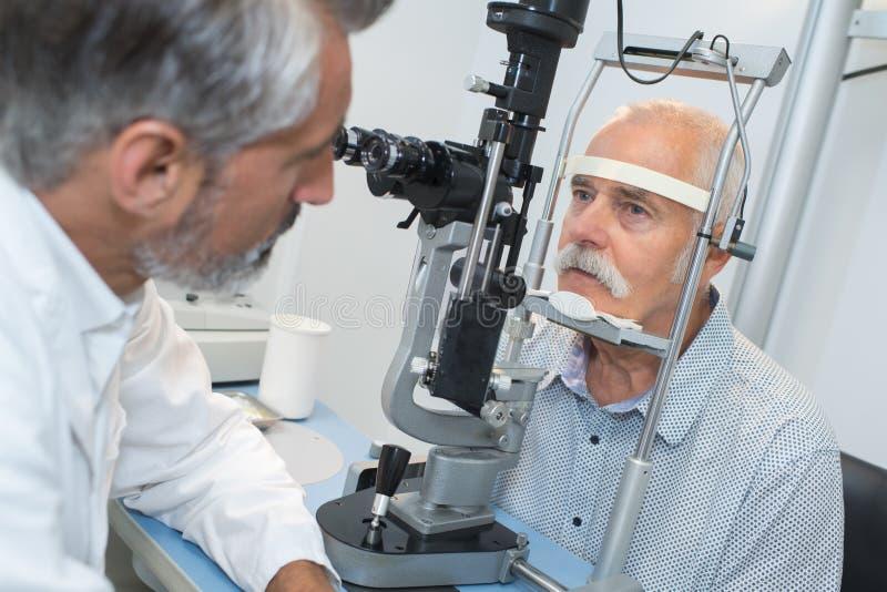 有青光眼的年长人在光学考试的眼镜师 图库摄影