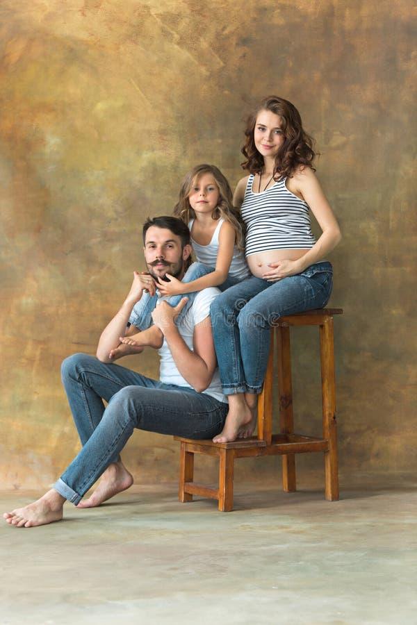 有青少年的女儿和丈夫的怀孕的母亲 家庭在棕色背景的演播室画象 免版税库存照片