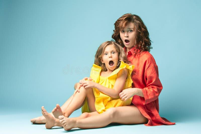 有青少年的女儿的怀孕的母亲 家庭在蓝色背景的演播室画象 免版税图库摄影