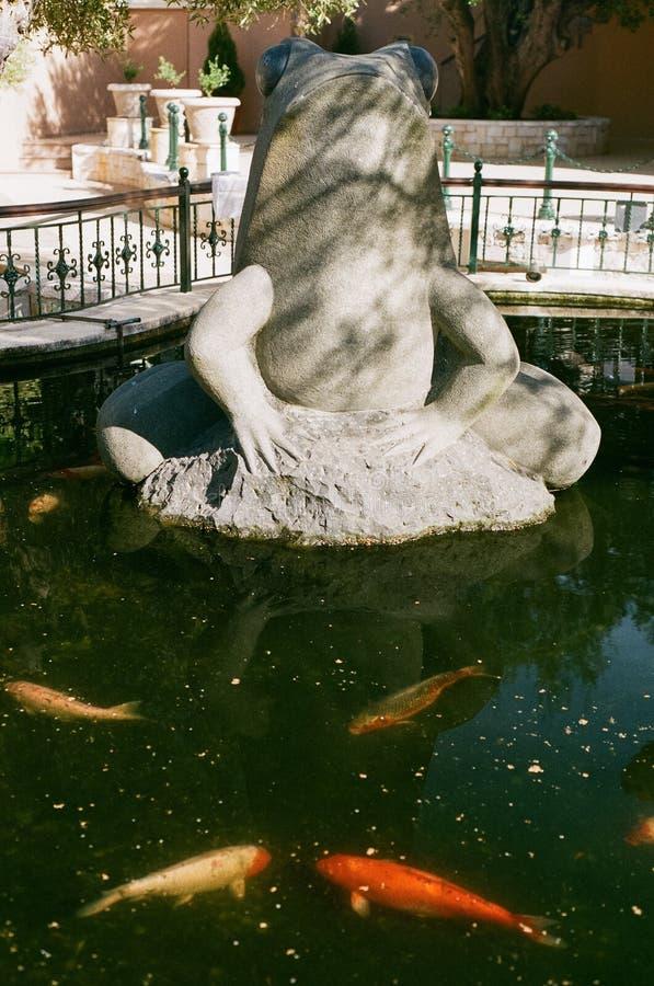 有青蛙雕塑的鱼池 免版税库存图片