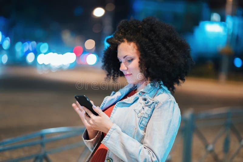 有非常卷曲非洲的头发的年轻美丽的妇女使用手机在晚上照亮了街道 异常的时髦女孩与 免版税库存照片