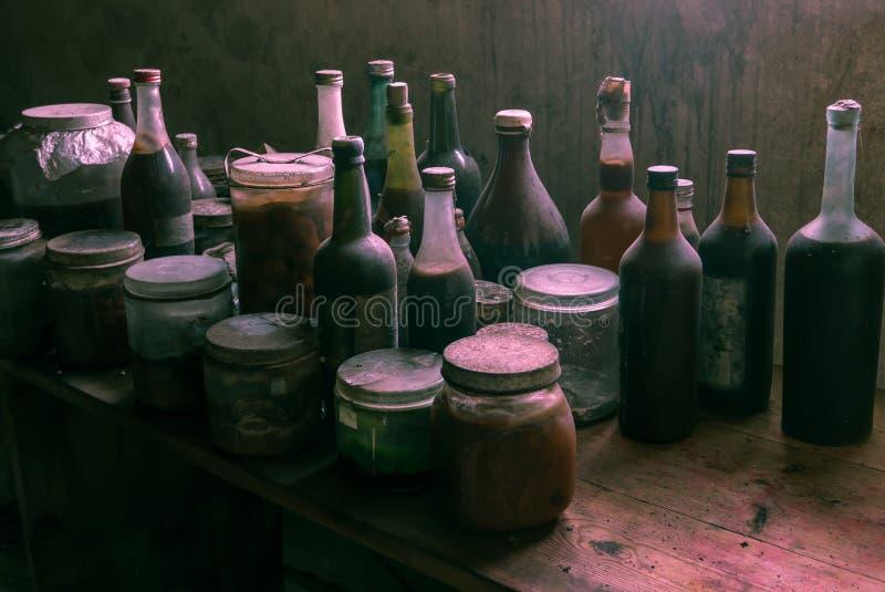 有非常可疑内容的多灰尘的老玻璃瓶 免版税库存图片
