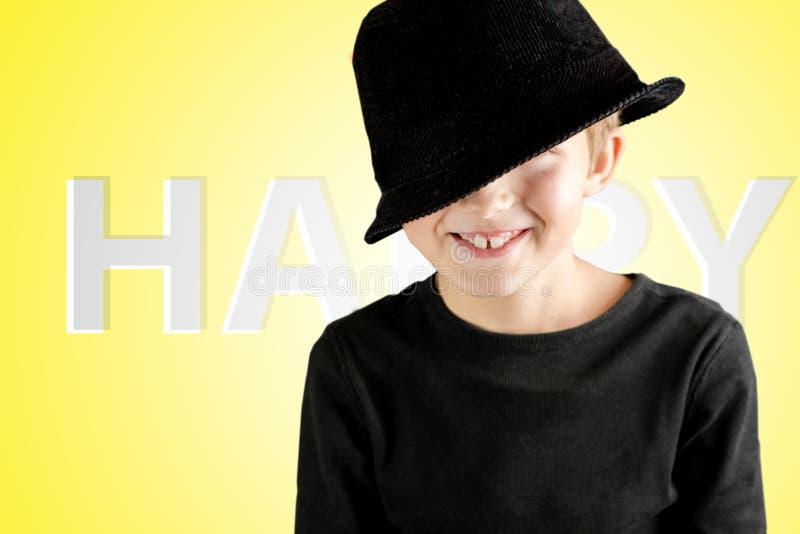 有非常愉快和美满的姿态的微笑的年轻男孩在黄色背景 免版税图库摄影
