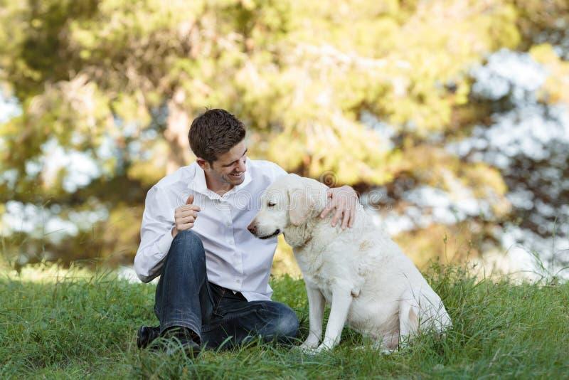 有非常老狗的年轻白种人人在公园 免版税库存照片