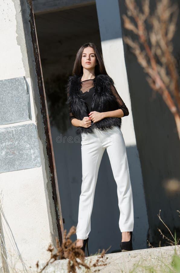 有非常长的头发穿戴脚跟和白色裤子的小的少妇 库存图片