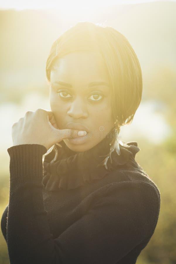 有非洲出现的妇女反对阳光,轻的背景,defocused 镇静轻松的面孔的女孩接触肉欲 免版税库存照片