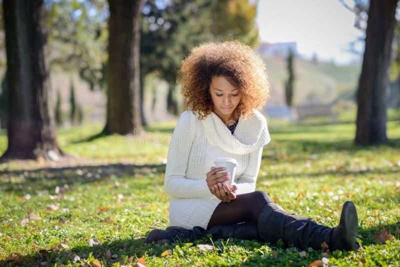有非洲的发型的年轻非裔美国人的女孩与咖啡杯 图库摄影
