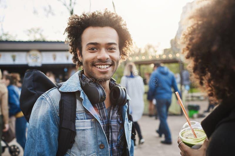 有非洲的发型的正面和迷人的深色皮肤的人走与女朋友的在公园,广泛地微笑对照相机 免版税库存图片