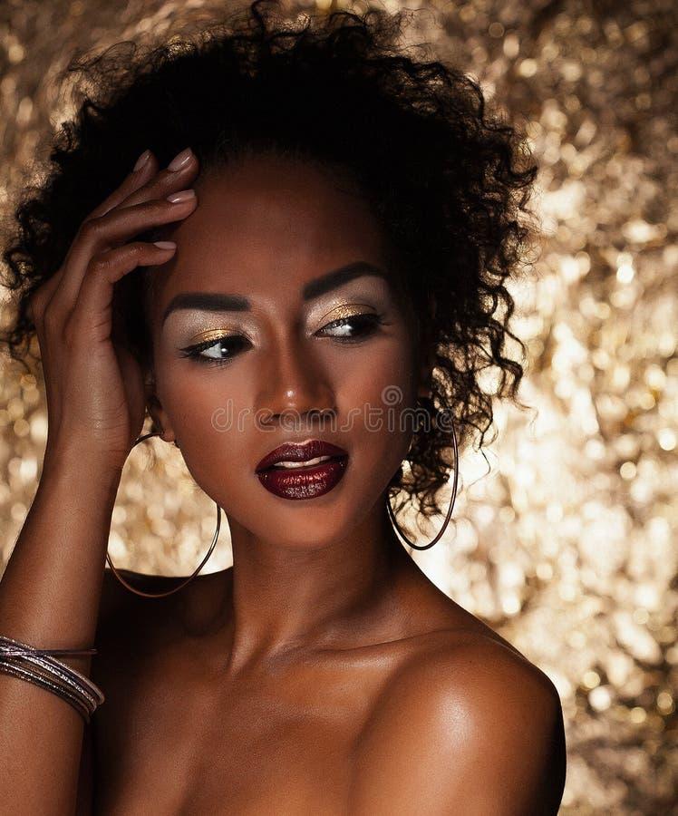有非洲的头发的年轻典雅的非裔美国人的妇女 魅力构成 金黄的背景 免版税库存图片