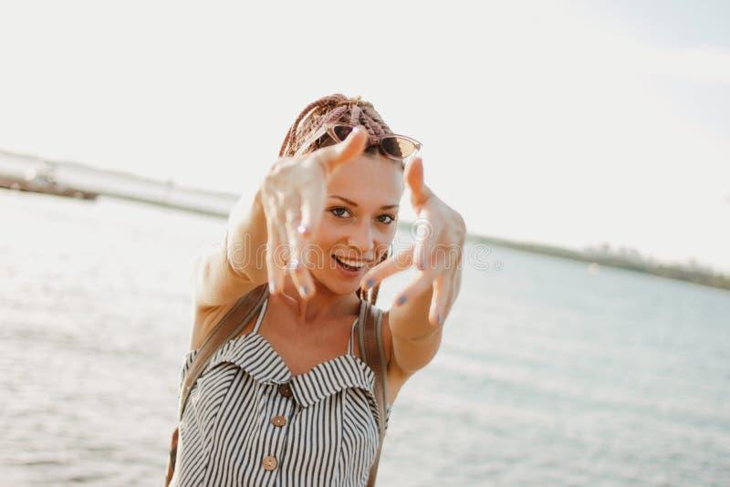 有非洲辫子的愉快的无忧无虑的年轻女人享有她的在海滩的生活,暑假时间 库存照片