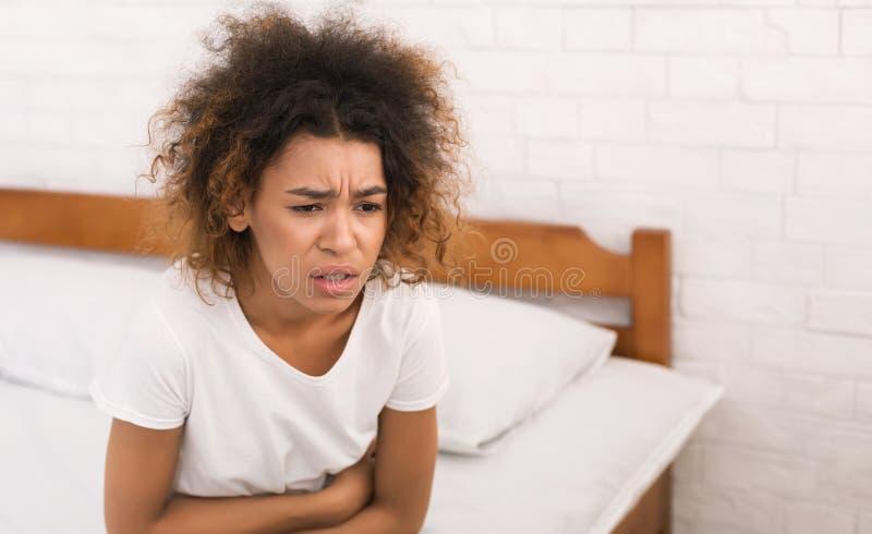 有非裔美国人的妇女痛苦的stomachache,坐床 库存图片