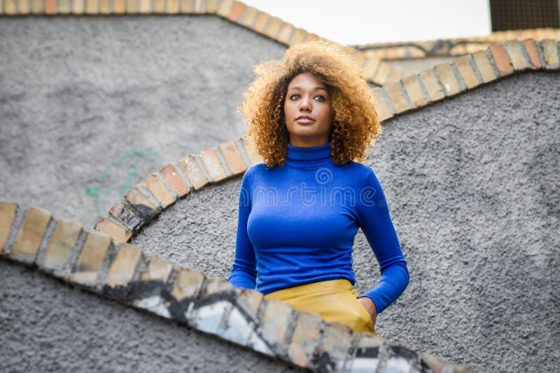 有非洲的发型的女孩在都市背景中 图库摄影